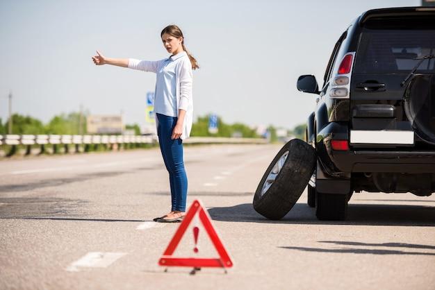La niña se para con la mano levantada y atrapa un automóvil que pasa. Foto Premium