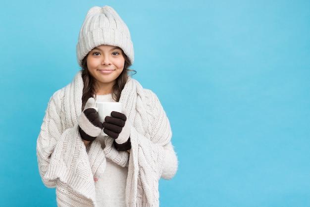 Niña con manta y sosteniendo la taza con té Foto gratis