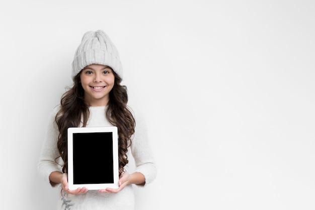 Niña con maqueta de dispositivo de tableta Foto gratis