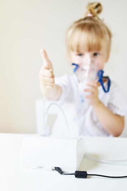 Niña en una máscara para inhalaciones, haciendo inhalación con nebulizador en casa inhalador sobre la mesa, niño enfermo interior Foto Premium