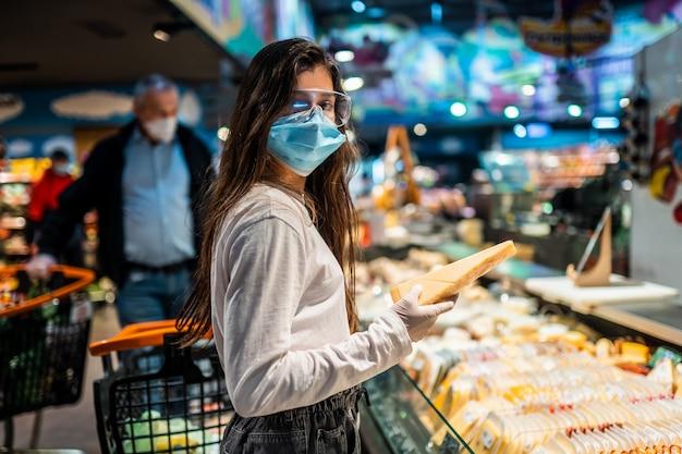 La niña con mascarilla quirúrgica va a comprar queso. Foto gratis