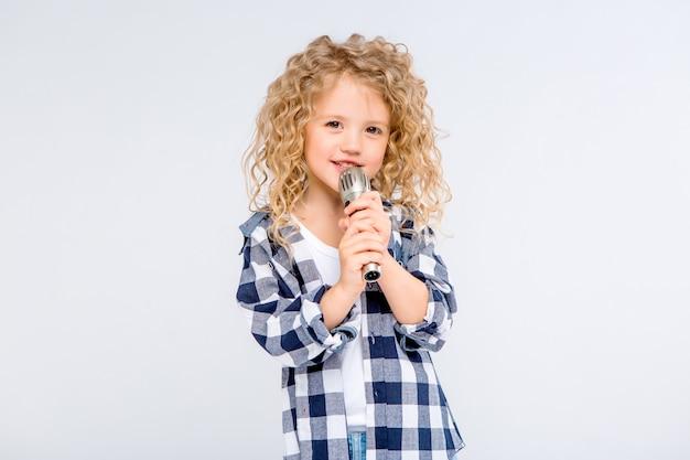 Niña con micrófono sonriendo cantando Foto Premium