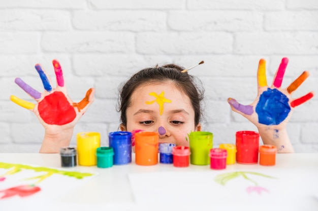Niña mirando botellas de pintura multicolor en el escritorio blanco con sus palmas pintadas Foto gratis