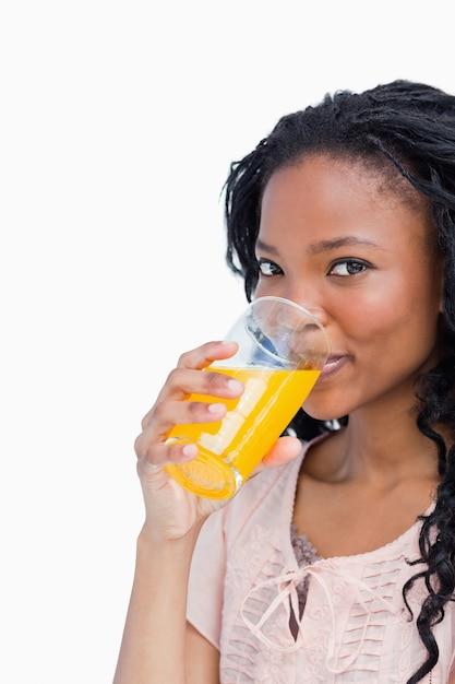 2ac7f2006 Una niña mirando a la cámara está tomando jugo de naranja ...