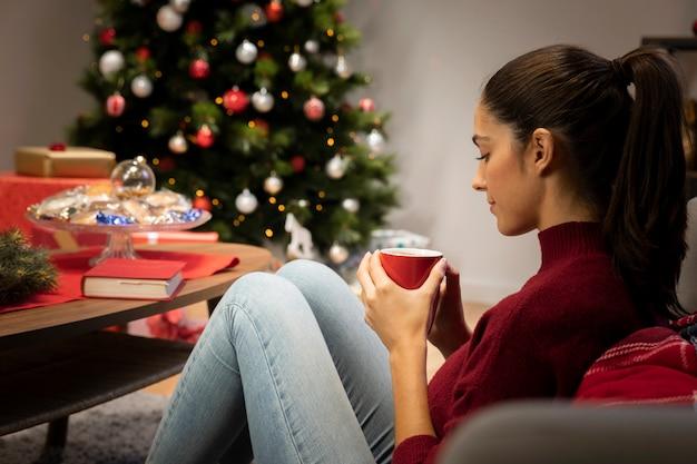 Niña mirando una taza con un fondo de navidad Foto gratis