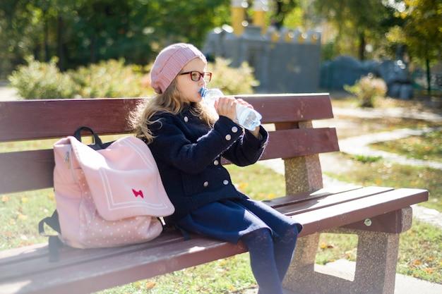 Niña con mochila escolar, agua potable. Foto Premium