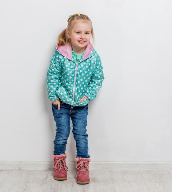 Niña de moda en jeans, chaqueta y botas Foto Premium