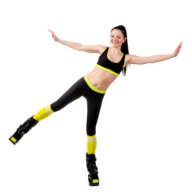 Niña morena sonriente con entrenamiento de pelo largo en un kangoo salta zapatos. Foto Premium