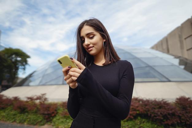 Niña morena usando su teléfono celular mientras explora una nueva ciudad Foto gratis