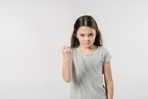 Niña mostrando el puño en el estudio Foto gratis
