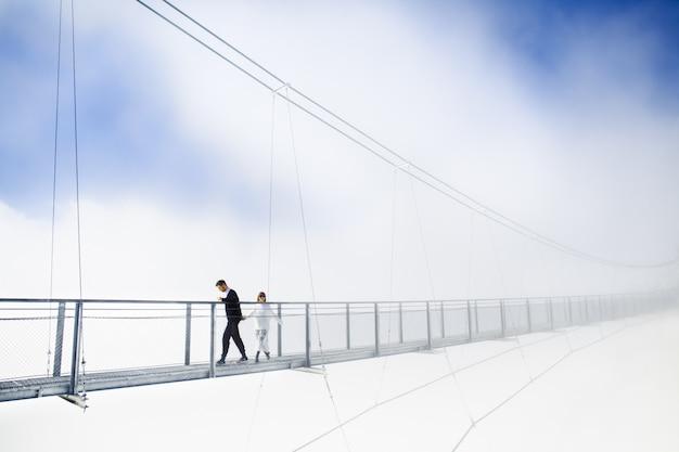 Niña y niño caminando sobre el puente en las nubes Foto gratis