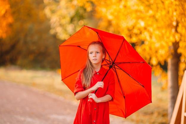 Niña niño feliz se ríe bajo el paraguas rojo Foto Premium