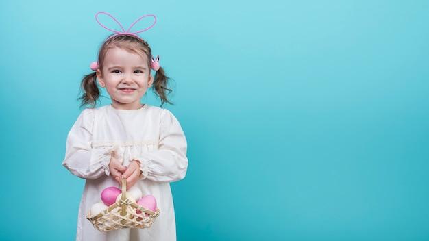 Niña en orejas de conejo con canasta con huevos de pascua Foto gratis