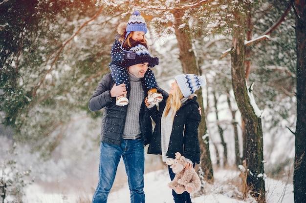 Niña con padres jugando en un parque de invierno Foto gratis
