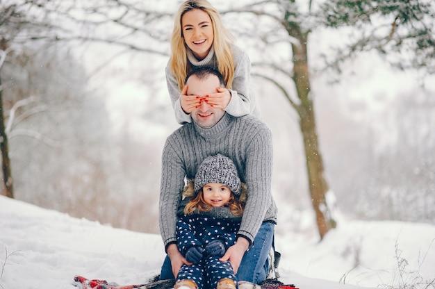 Niña con padres sentados sobre una manta en un parque de invierno Foto gratis