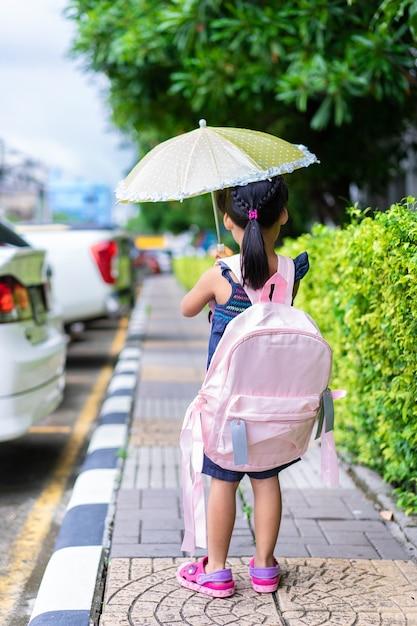 Niña con paraguas y mochila caminando en el parque listo de regreso a la escuela en el día lloviendo Foto Premium