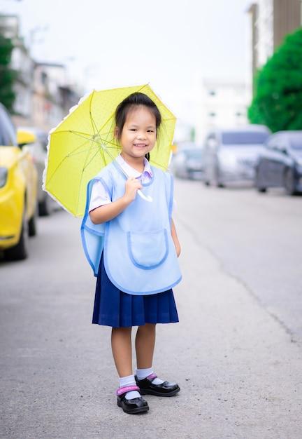 Niña con paraguas de pie en el aparcamiento listo para volver a la escuela en llover día Foto Premium