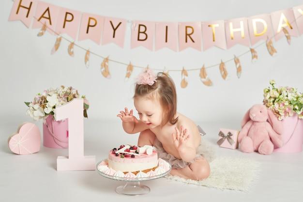 Niña con un pastel de cumpleaños, sesión de fotos de bebé de 1 año Foto Premium
