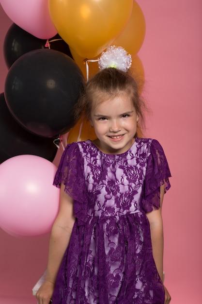 Niña de pelo oscura con globos de colores sobre fondo rosa Foto Premium