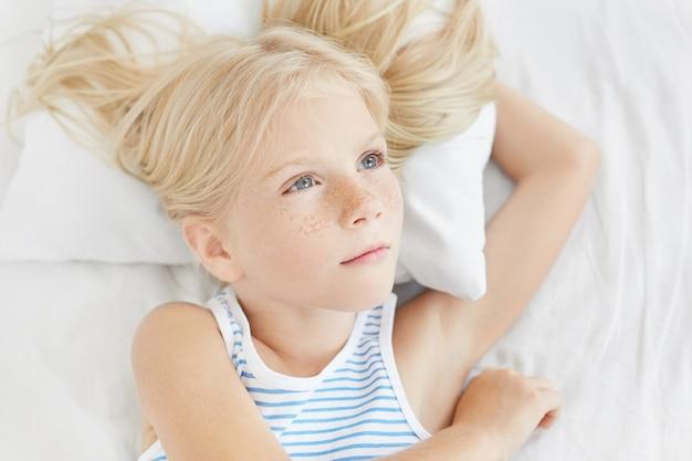 Niña pensativa con ojos azules y pestañas largas, cabello largo y rubio, con camiseta de marinero, acostada sobre una almohada blanca, mirando a un lado Foto gratis