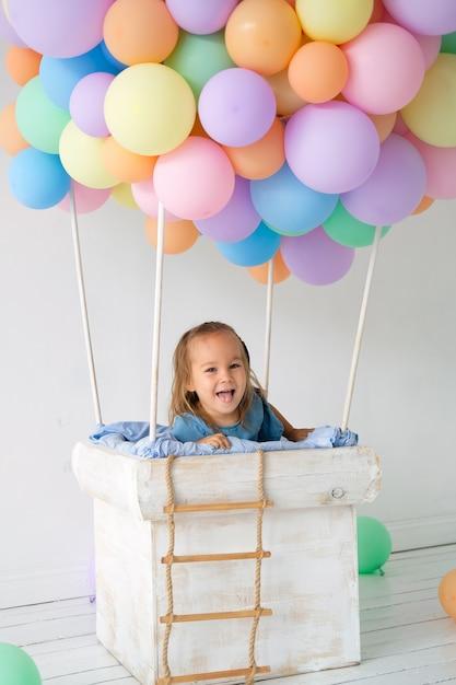 Una niña pequeña se para en una canasta de globos y se ríe. cumpleaños, decoraciones navideñas Foto Premium