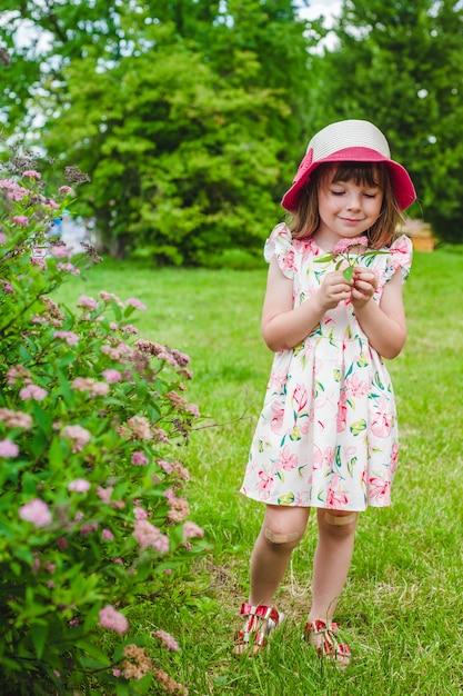 Niña pequeña con unas flores en la mano | Descargar Fotos gratis
