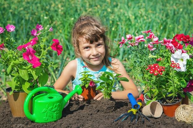 Una niña pequeña está plantando flores. Foto Premium