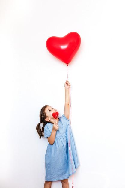 Una niña pequeña que sostiene un hermoso globo rojo en forma de corazón para un regalo de san valentín y una piruleta en forma de corazón, amantes, día de san valentín, familia y corazón Foto Premium