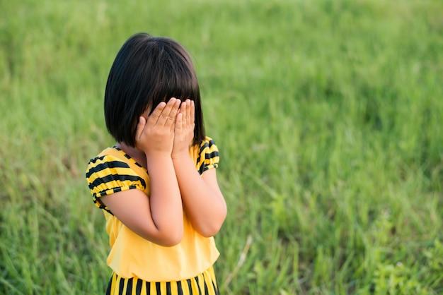 Niña pequeña tapándose la cara Foto gratis