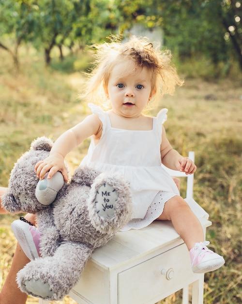 Niña pequeña con un vestido y un oso de peluche Foto gratis