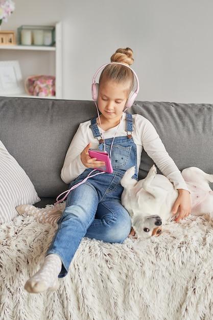 Niña y perro acostado en el sofá con auriculares, escuchando música con su teléfono inteligente Foto Premium