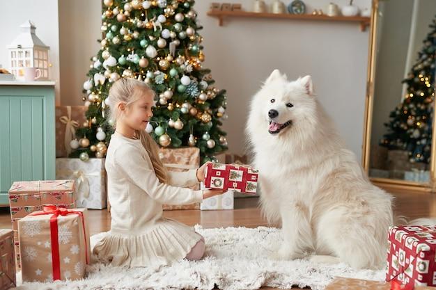 Niña con un perro cerca del árbol de navidad en la escena navideña Foto Premium