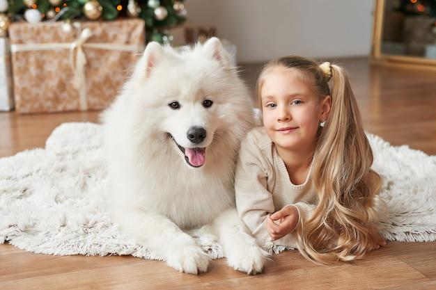 Niña con un perro cerca del árbol de navidad Foto Premium