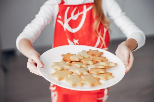 Niña de pie en una cocina con galletas Foto gratis