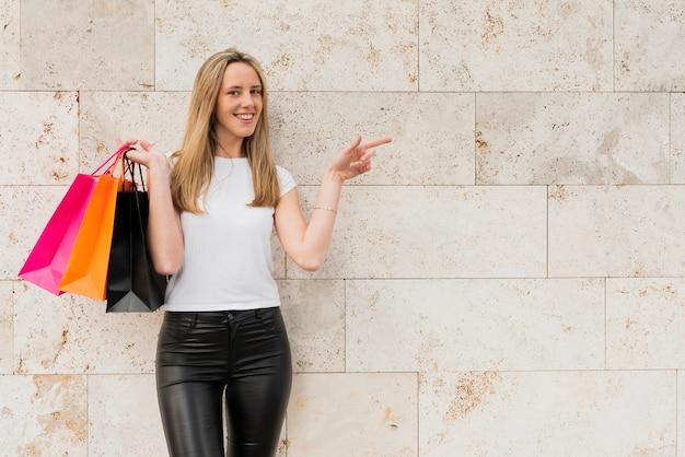 Niña de pie junto a la pared con bolsas de compras Foto gratis