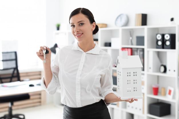 Una niña de pie en la oficina y sosteniendo las llaves y el diseño de la casa. Foto Premium