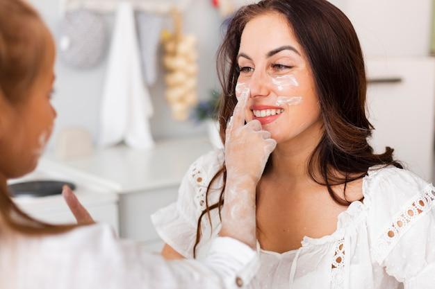 Niña pintando con harina su cara de madre Foto gratis