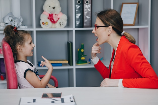 Niña preescolar pequeña niña hablando practicando la articulación de sonidos durante una clase privada con la madre de los padres Foto Premium