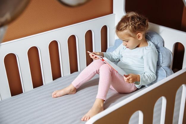 Niña que lee un libro en el dormitorio. Foto Premium