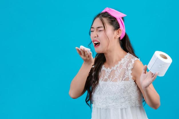La niña que lleva un pijama blanco no se siente cómoda. usando pañuelos para limpiarse la nariz con un azul. Foto gratis