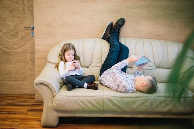Niña que se sienta cerca de su hermano que mira la tableta digital en el sofá en casa Foto gratis