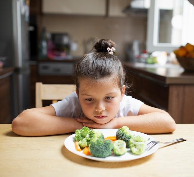 Niña rechazando alimentos saludables Foto gratis