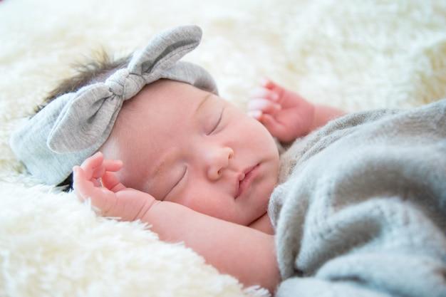 3bf7e639c La niña recién nacida está durmiendo en manta de piel