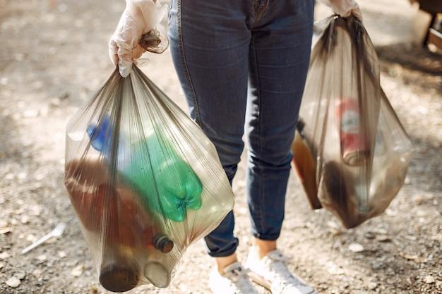 Niña recoge basura en bolsas de basura en el parque Foto gratis