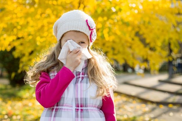 Niña con rinitis fría sobre fondo de otoño Foto Premium