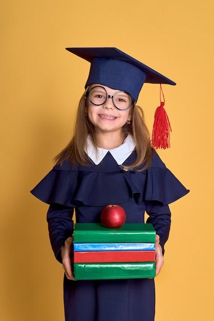Niña en ropa académica con libro Foto Premium