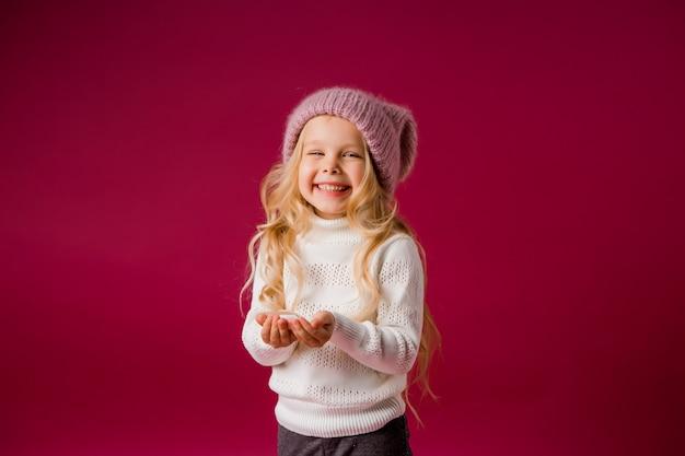 Niña rubia con gorro de punto y suéter juega con la nieve Foto Premium