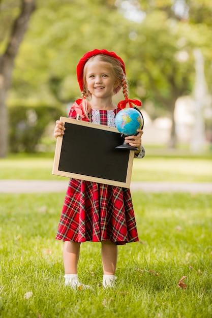 Niña rubia de primer grado en vestido rojo y boina sosteniendo un tablero de dibujo vacío y globo Foto Premium