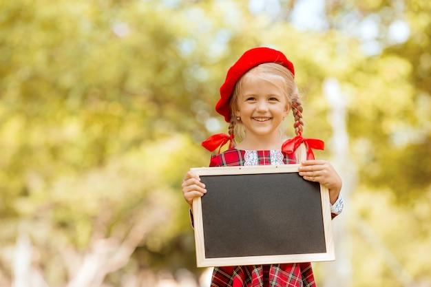 Niña rubia de primer grado en vestido rojo y boina sosteniendo un tablero de dibujo vacío Foto Premium
