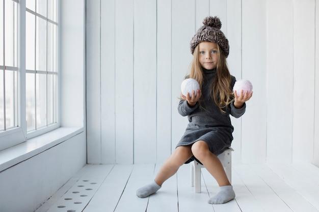 Niña rubia que ofrece bolas de nieve Foto gratis